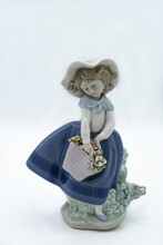 Ancient Porcelain Figure, It Is A Doll Or A Woman With A Hat, Long Skirt And A Basket Of Flowers. It Is Hand Painted