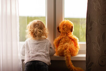 A Small Blonde Girl A Child A Boy Is Standing With His Back Looking Out Of The Window A Toy Red Monkey Is Standing Next To Him