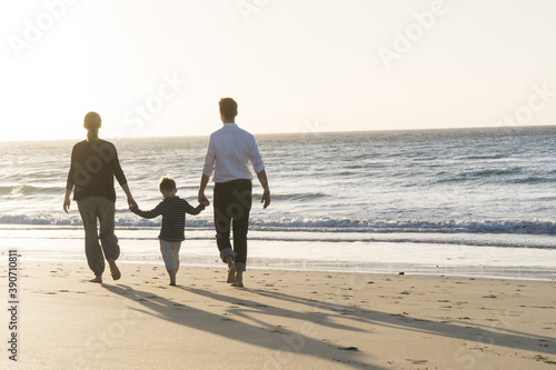 Canvas Print Family of three walking on the seashore during sunset