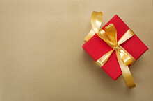 Red Gift Box With Gold Ribbon And Bow On Gold Background