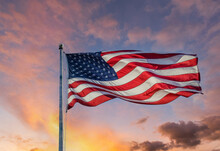 An American Flag Backlit By The Sun Against A Blue Sky With Clouds