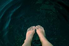 Woman's Feet In River Water