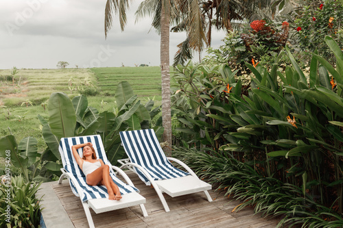 Portrait of young woman chilling in the tropical sun near swimming pool on a deck chair with palm trees behind Fototapet