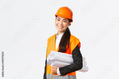 Smiling successful asian female architect, construction engineer in safety helmet, carry blueprints and smiling happy at camera, introduce building project, standing white background