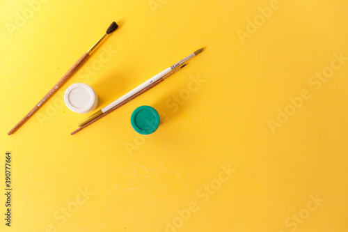 Brushes and paints on a yellow background, top view, with space for text Wallpaper Mural