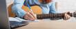 Leinwandbild Motiv A woman with a guitar writes notes in a notebook. The girl composes a song
