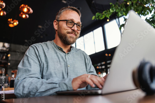 Obraz Middle aged bearded smiling freelancer with eyeglasses sitting in a restaurant and using laptop to type report. Middle aged persons can be excellent freelancers. - fototapety do salonu