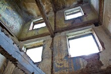 An Abandoned Brick Building With Windows. A Photo Inside A House Commune With A View On Ceiling.