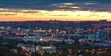 Cityscape Of Smolensk At The Sunset: Lit Up Street Lamps Among Buildings And Houses And Cloudy Orange Sky Over It In Russia.