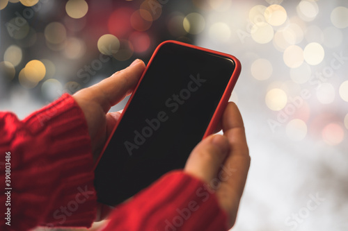 Canvastavla Cropped of woman's hands in red sweater holding smartphone with blank screen of gadget at Christmas time