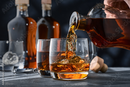 Two glasses of whiskey with ice on a concrete table, a glass of whiskey is poured from a bottle Fotobehang
