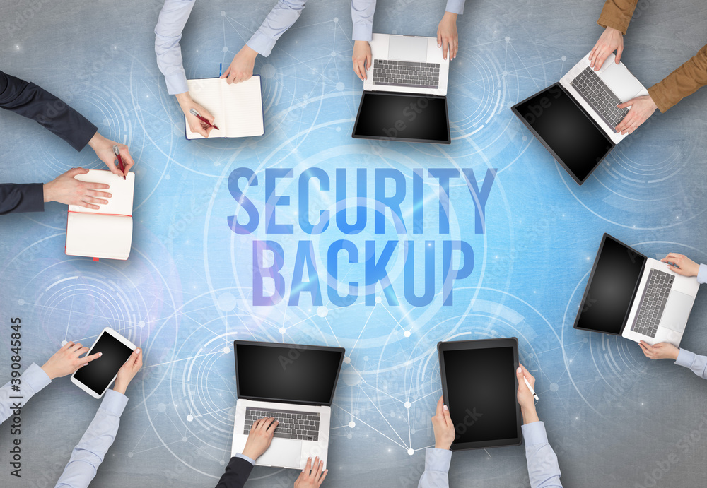 Fototapeta Group of people in front of a laptop with SECURITY BACKUP insciption, web security concept