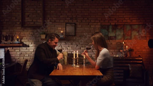 Tela Elegant couple having romantic dinner at home, sitting at table in living room drinking red wine