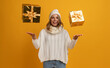 young smiling happy pretty woman with golden present boxes celebrating new year, christmas gifts, wearing white knitted sweater, scarf and hat, winter fashion trend, posing on yellow background
