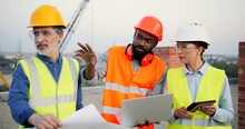 Caucasian And African American Males And Female Builders, Architector And Engineers With Draft Plan Of Building And Laptop Computer Talking On Constructing Site. Mixed-races Men And Woman Constructors