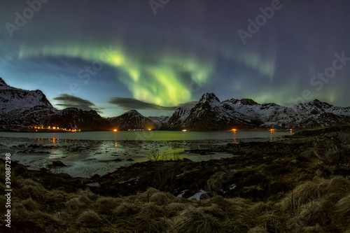 Fototapeta panoramica de aurora boreal entre montañas frente a un lago