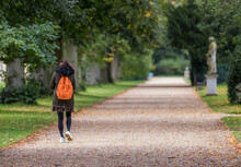 Woman Walking Away From Camera Along Gravel Path With Orange Rucksack, The Distance Is Blurred