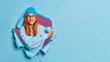 Crazy happy ginger woman poses in torn blue paper background indicates away on copy space shows awesome advertisement or sale dressed in casual jumper and hat. Banner for discounts or advertising text
