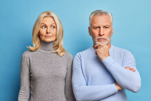 Serious Mature Woman And Man Stand Closely To Each Other Have Thoughtful Expressions Dressed In Casual Clothes Isolated Over Blue Background. Self Confident Bearded Male Pensioner Holds Chin