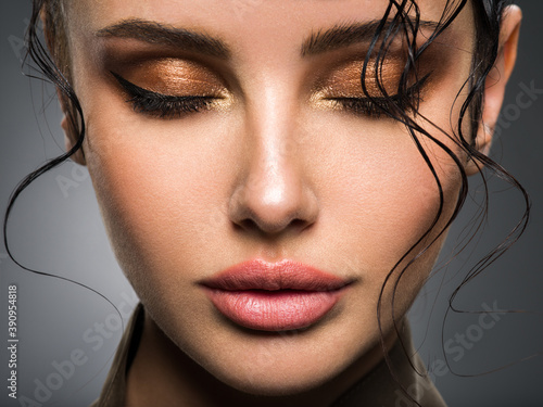 Closeup portrait of a beautiful young fashion woman with glamour makeup posing at studio.