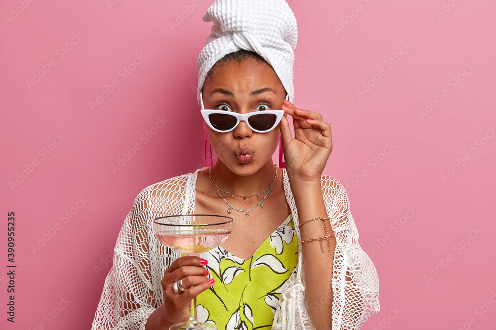 Fototapeta Studio shot of lovely dark skinned woman looks with flirty romantic expression at camera keeps lips folded drinks martini cocktail wears trendy sunglasses bath towel on head isolated over rosy wall