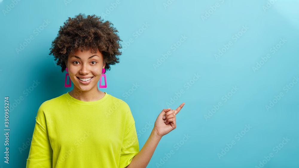 Fototapeta Horizontal shot of cheerful Afro American woman in casual t shirt points away on copy space suggests follow this direction or click on link poses against blue background. Your advertising here