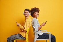 Addicted Interracial Woman And Man Sit Back To Each Other On Comfortable Chairs Hold Mobile Phones And Have Happy Expressions Spend Free Time At Home On Self Isolation Isolated Over Yellow Background