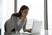 Just A Minute. Thoughtful Interested Young Female Office Worker Standing Near Desk With Laptop Looking On Screen With Smile Inspired By Good Idea Checking Sudden Thought Online Getting Awaited Email