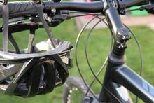 A Bicycle Helmet Hangs On The Handlebars Of A Mountain Bike