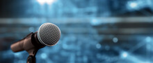 Public Speaking Backgrounds, Close-up The Microphone On Stand For Speaker Speech At Seminar Room With Technology Light Background And Blur Bokeh.