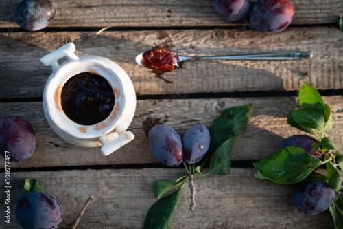 plum jam in a white ceramic pot on an aged wooden background, fresh plums near Fototapeta