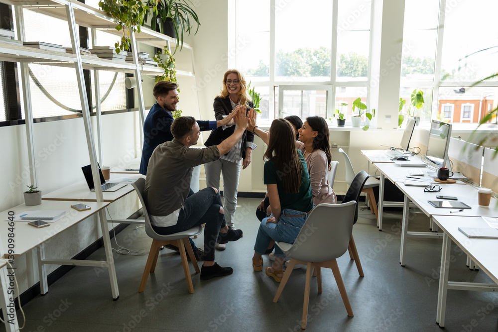 Fototapeta Celebrating success. Multiethnic millennial corporate staff and older woman trainer leader stacking hands in high five gesture greeting colleagues with business victory team achievement winning reward