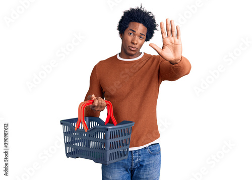 Fotografía Handsome african american man with afro hair holding supermarket shopping basket