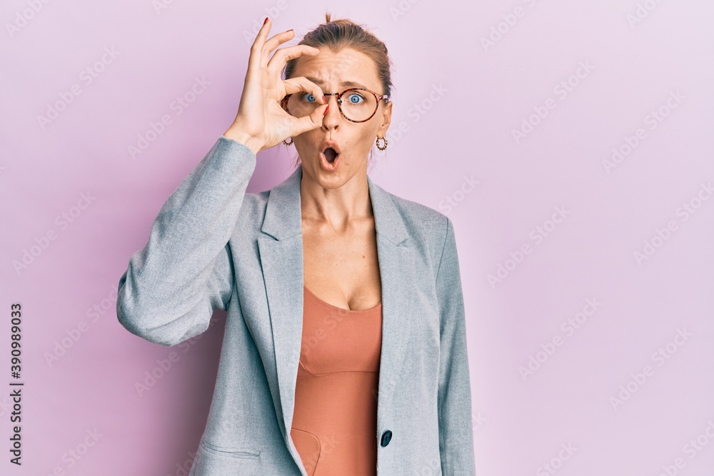Fototapeta Beautiful caucasian woman wearing business jacket and glasses doing ok gesture shocked with surprised face, eye looking through fingers. unbelieving expression.