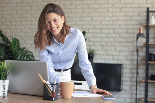 Obraz Young business woman standing in her home office writing notes. - fototapety do salonu