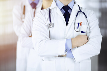 Group of modern doctors standing as a team with crossed arms and stethoscopes in a sunny hospital office. Physicians ready to examine and help patients. Medical help, insurance in health care, best