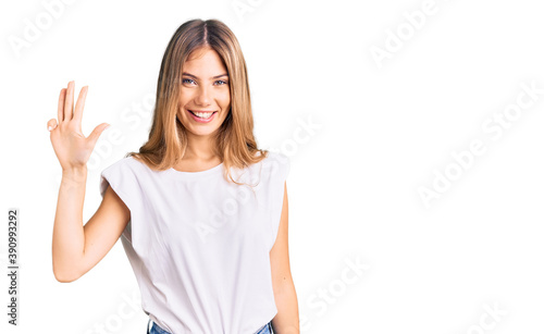 Foto Beautiful caucasian woman with blonde hair wearing casual white tshirt showing and pointing up with fingers number four while smiling confident and happy