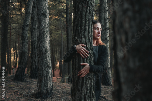 Cuadros en Lienzo The beautiful woman is hagging trees, Girl loves nature and standing in the autu