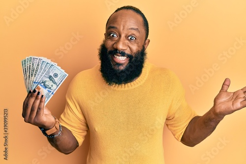 Fototapety, obrazy: Young african american man holding dollars celebrating achievement with happy smile and winner expression with raised hand