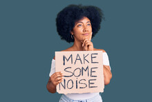 Young African American Girl Holding Make Some Noise Banner Serious Face Thinking About Question With Hand On Chin, Thoughtful About Confusing Idea