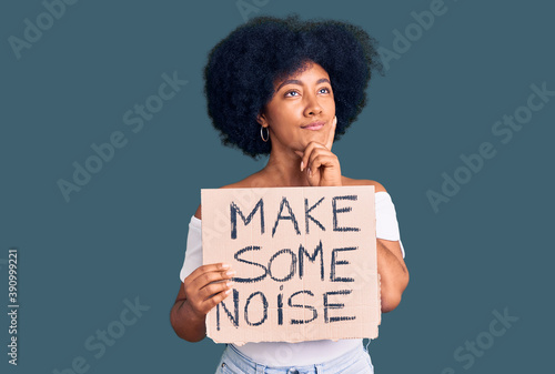 Canvas Print Young african american girl holding make some noise banner serious face thinking