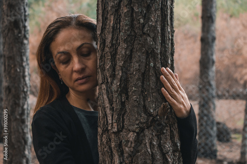 Fotografía The beautiful woman is hagging trees, Girl loves nature and standing in the autu