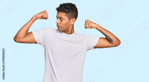 Young handsome african american man wearing casual white tshirt showing arms muscles smiling proud Fototapet