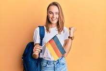 Beautiful Blonde Woman Exchange Student Holding Germany Flag Pointing Thumb Up To The Side Smiling Happy With Open Mouth