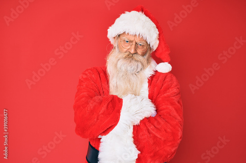 Slika na platnu Old senior man with grey hair and long beard wearing traditional santa claus costume skeptic and nervous, disapproving expression on face with crossed arms