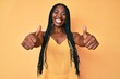 African american woman with braids wearing casual clothes approving doing positive gesture with hand, thumbs up smiling and happy for success. winner gesture.