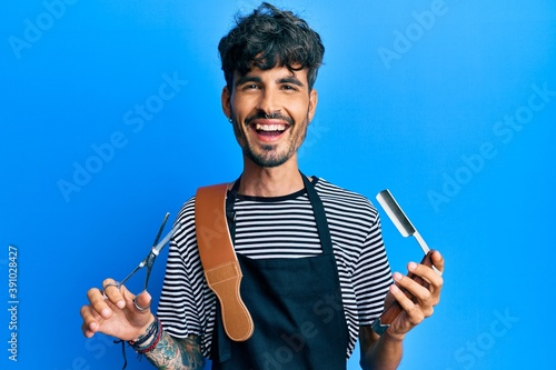 Photo Young hispanic man wearing barber apron holding razor and scissors smiling and laughing hard out loud because funny crazy joke