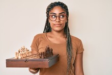 Young African American Woman With Braids Holding Chess Board Wearing Glasses Smiling Looking To The Side And Staring Away Thinking.