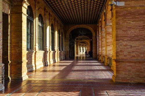 Interior Plaza de España en Sevilla al atardecer en un día soleado, galería que recorre el monumento público.