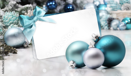Fototapeta merry christmas gift card with bow and ribbon, next to blue Christmas balls, useful as a greeting card template with copy space obraz